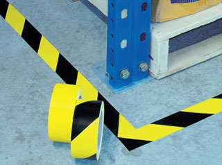 Safety marking tape black yellow stripes on floor at warehouse